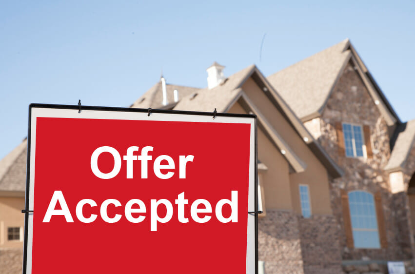 Sign in front of home for sale with the words 'offer accepted'