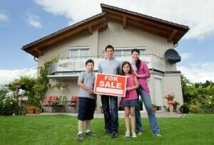 family standing in front of house with a sloped roof holding a for sale sign