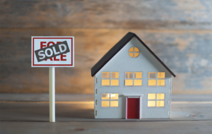 miniature model of a house with a sold sign next to it
