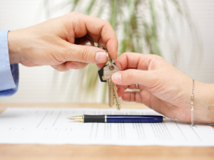realtor's hand giving keys to a home buyer